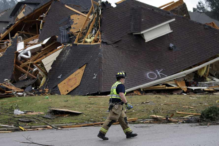 A firefighter surveys damage to a house in Eagle Point.