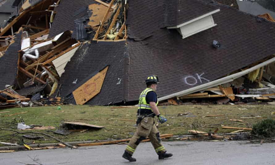 A firefighter surveyed damage to a house after a tornado touched down south of Birmingham, Alabama Thursday.