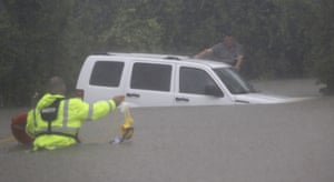 Wilford Martinez, right, waits to be rescued by Harris County Sheriff's Department Richard Wagner after his car got stuck in floodwaters