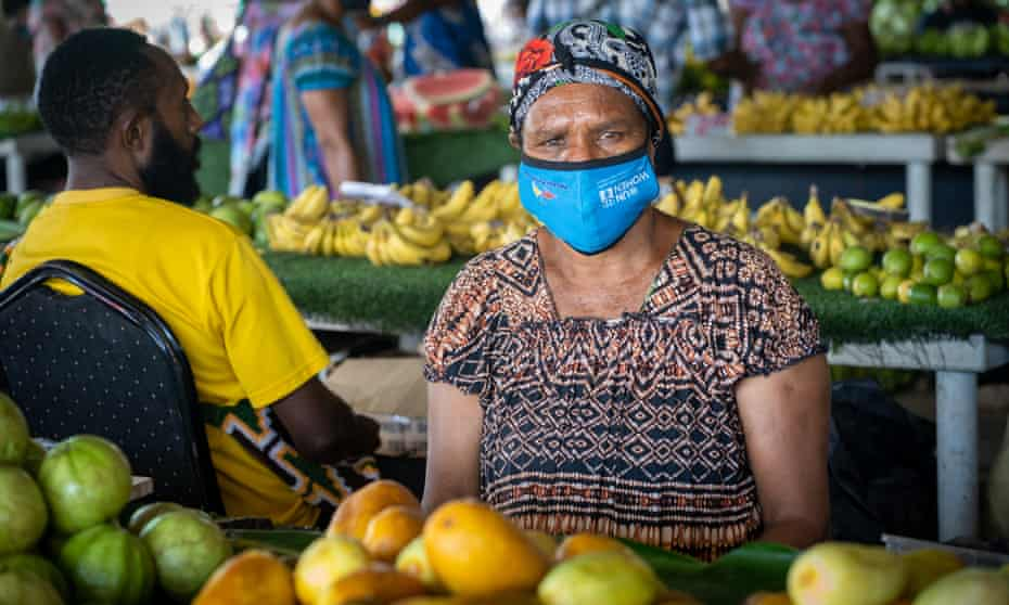A market seller at the Gordon's Market Place in Port Moresby wears a mask while she sells her fresh produce.