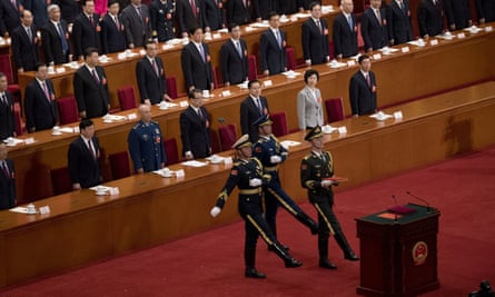 Soldiers carry a copy of the constitution into the people's congress meeting in Beijing on Saturday as Xi and his leadership team look on.