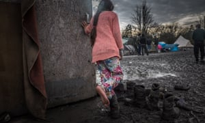 A girl tries on mud-caked boots in the camp.