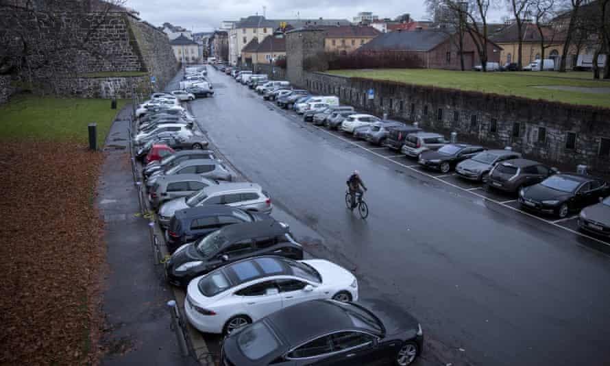 A cyclist rides past electric vehicles parked at charging stations at Kongens gate near Akershus festning in Oslo, Norway.