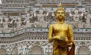 A Buddha statue stands in front of the ancient pagoda at the Wat Arun, or Temple of Dawn, in Bangkok, Thailand