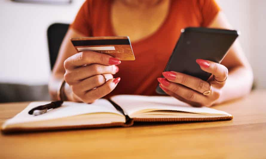 Woman looking at a debit card in one hand with her smartphone in the other