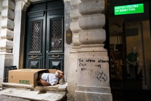 Athens, Greece A homeless man sleeps in a cardboard box outside a closed shop