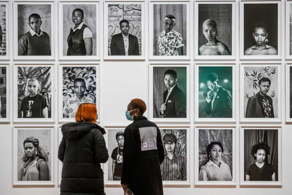 Tate visitors study portraits from the artist's ongoing series Faces and Phases.
