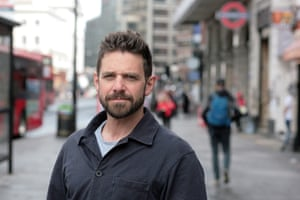 John Poyton standing on the pavement on a London street