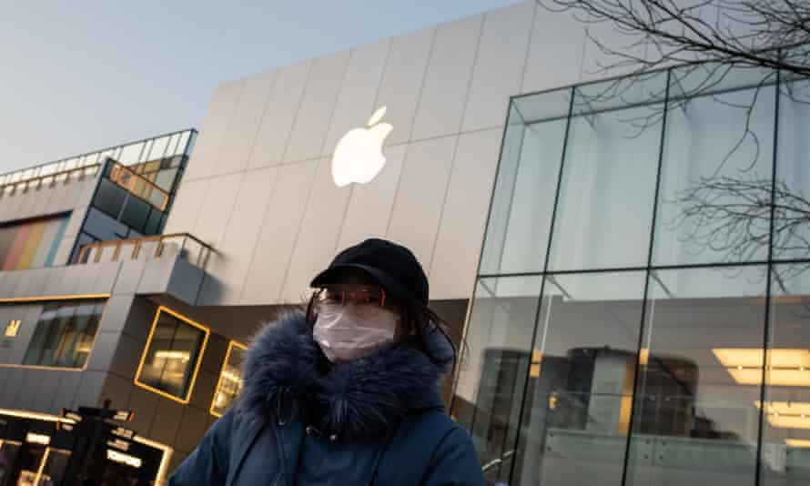 A woman in a face mask outside a closed Apple Store in Beijing