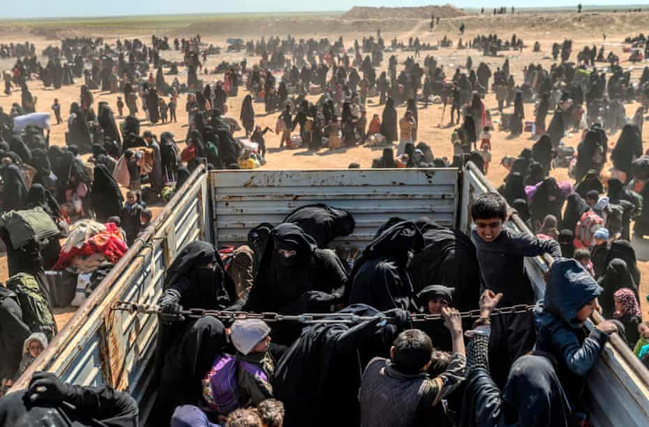 Women and children evacuated from Baghouz arrive at a screening area, in March last year