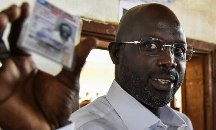 George Weah shows his voting card at the first round of Liberia's presidential election.