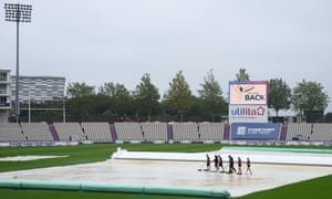 Groundstaff clear water from the covers on the third day of the second Test at Southampton