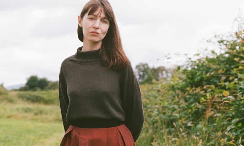The author Sally Rooney standing in the countryside.