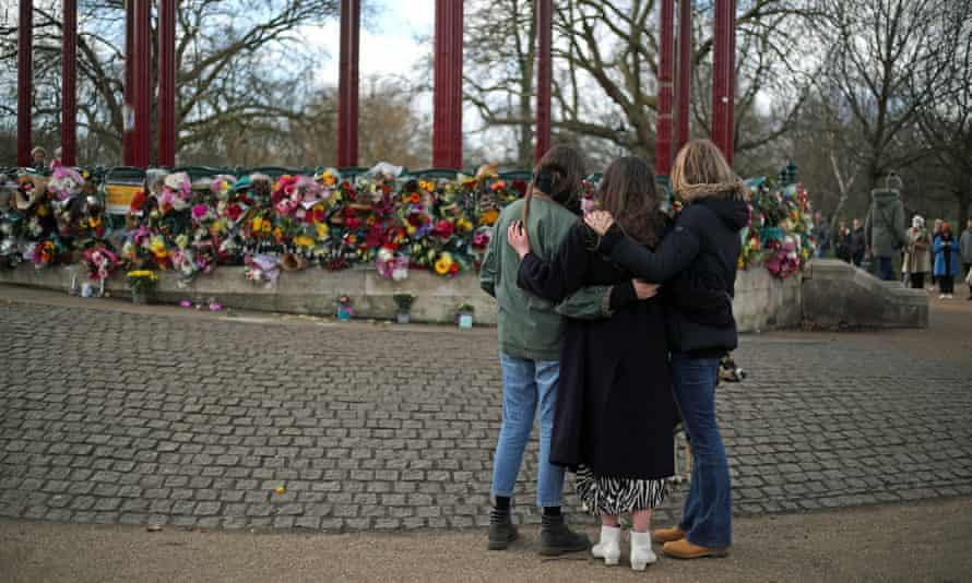People look at floral tributes for Sarah Everard at the band stand in Clapham Common, London