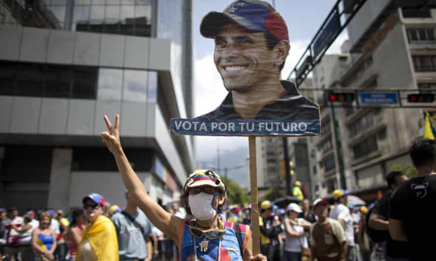 A woman holds up a banner with the image of opposition leader Henrique Capriles as people gather for a demonstration against Nicolas Maduro in Caracas.