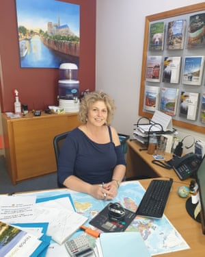 blonde woman sitting at a desk with travel brochures in background