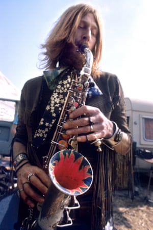 Nic Turner of Hawkwind - look at that ornate bell'Nic playing at Canvas City, a side show that allowed poetry, debate and experimental bands. Terry Ollis, Hawkwind's drummer, described how his one-hour drum solo was a ploy to stop panic in the audience while the tent was deflating. He then had to continue drumming when the tent was re-inflated and the band came on'