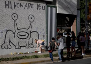 """A woman places flowers beneath the """"Hi, how are you"""" mural created by Daniel Johnston in Austin, Texas, 11 September 2019."""