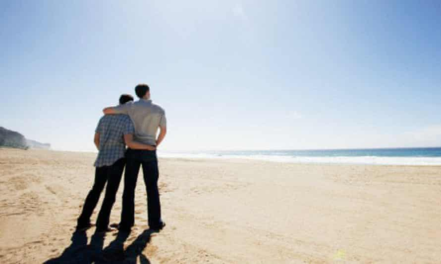 A gay couple with their arms around one another standing on a beach and looking out to sea