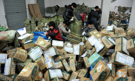 Chinese workers sort through boxes of goods at a delivery company in Lin'an, east China's Zhejiang province.