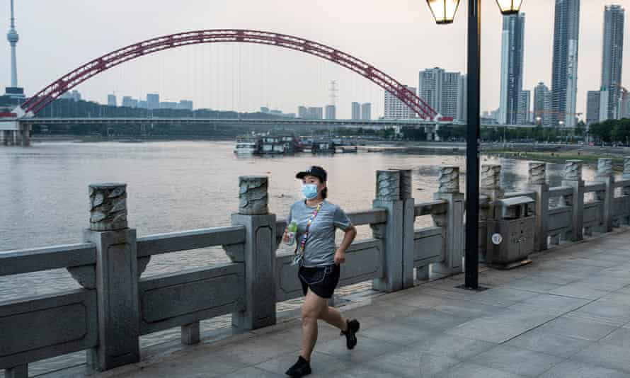 A women wears a mask while running near the Han River in dark night on August 1, 2021 in Wuhan, Hubei Province, China.