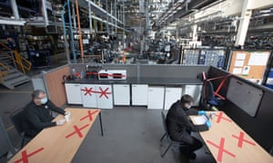 physically distanced workers sitting in a break area in  a Vauxhall car plant