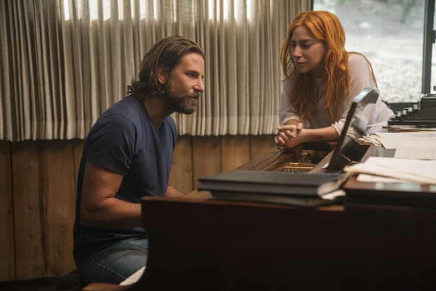 Bradley Cooper and Lady Gaga sit at a piano