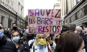 A man holds a sign that reads 'Save the bars and restaurants', during a demonstration against coronavirus restrictions in Marseille.