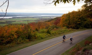 A pair of cyclists ride by the view from Gatineau Park.