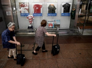Women walk past a shop displaying rugby jerseys in Kobe ahead of the tournament.