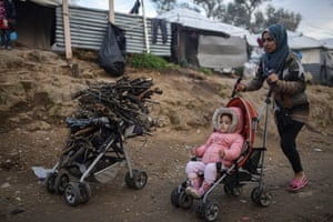 A woman and her baby pass a pram filled with firewood at a makeshift camp next to the camp of Moria on the island of Lesbos.