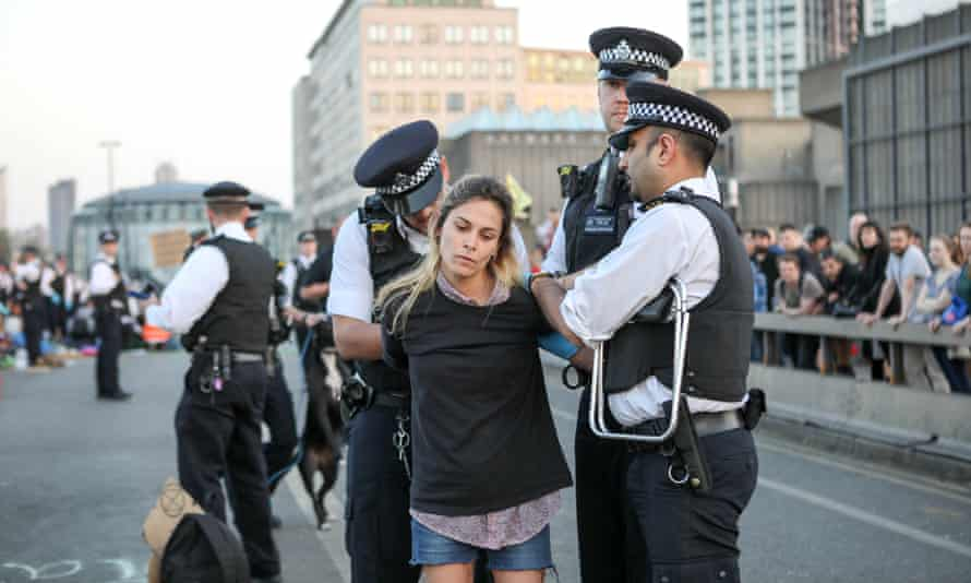 Police remove a Extinction Rebellion protester from Waterloo Bridge on Sunday evening.