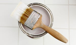 Paint brush and an open tin of white paint.