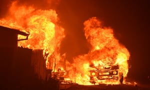 A car and house engulfed in flames