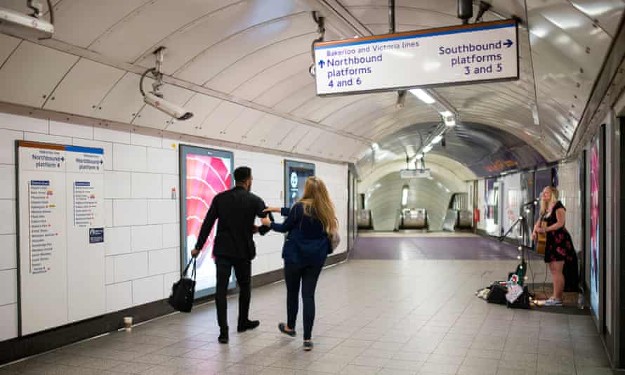 Charlotte Campbell busks at Oxford Circus as passengers walk by