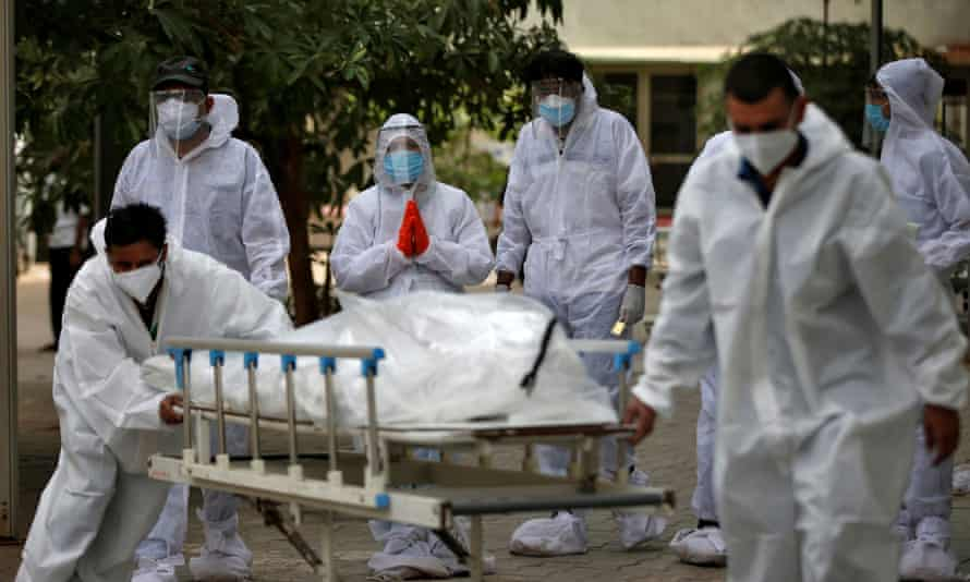 Healthcare workers pull a stretcher carrying the body of a person who died from coronavirus in Ahmedabad, India.