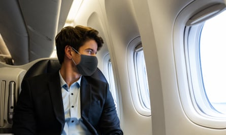 A young man wearing a face mask stares out of a large aeroplane porthole.