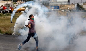 A Palestinian demonstrator uses a sling to hurl back a teargas canister fired by Israeli troops during a Nakba day protest near the Jewish settlement of Beit El, near Ramallah, in the occupied West Bank
