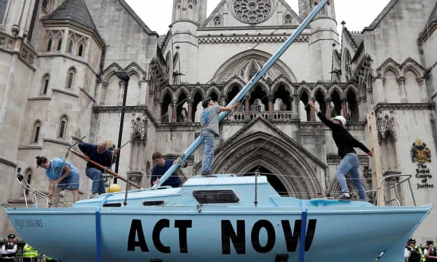 Extinction Rebellion activists raise a mast on their boat during a protest outside the royal courts of justice in London.