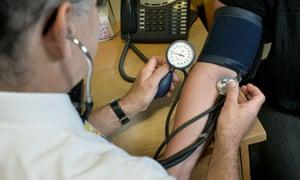 GP taking blood pressure.