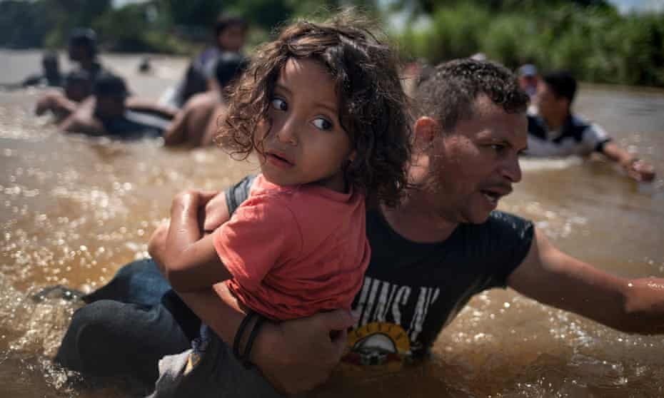 Luis Acosta keeps a tight grip on five-year-old Angel Jesus as a caravan of migrants crossed into Mexico from Guatemala.