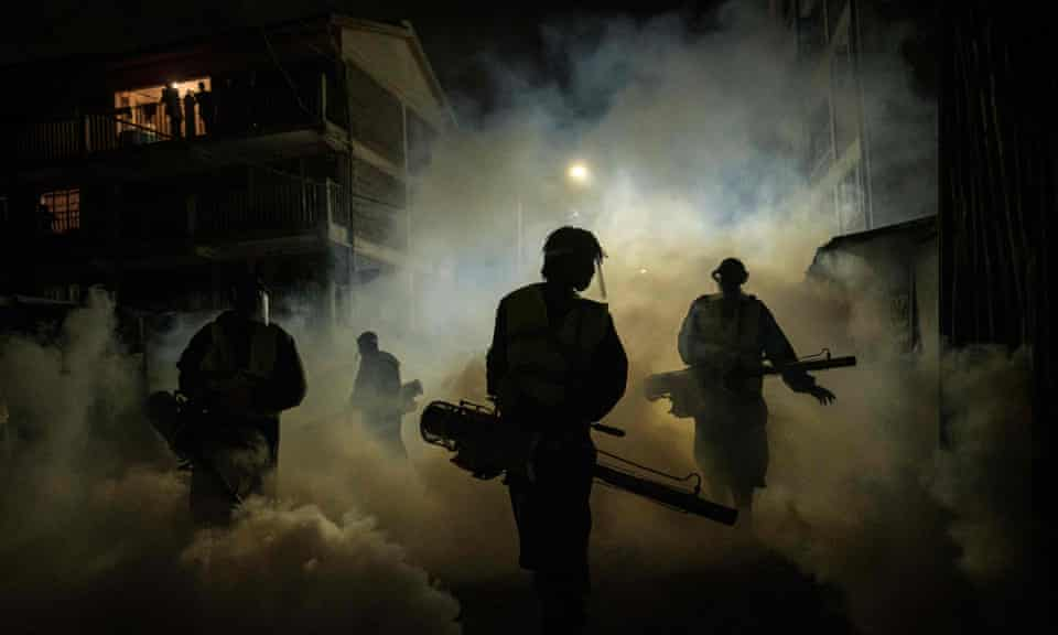 Volunteers fumigate a street in Nairobi in April.