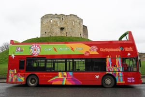 A sightseeing bus stands empty next to Clifford's Tower in York