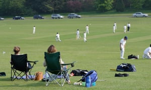 Parents watch their boys play cricket