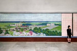 A platform attendant stands by a mosaic of a coastal scene in Konguk station.