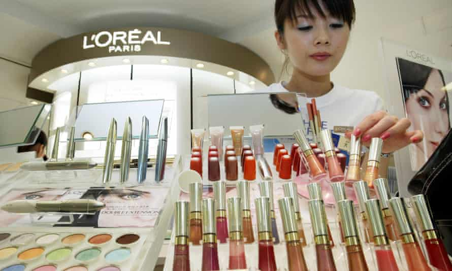 A beauty consultant adjusts cosmetics at a L'Oreal counter. The French firm has said it will phase out microbeads by 2017.