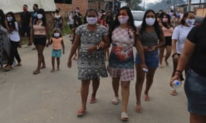 Locals walk after the funeral of Chief Messias Martins Moreira, 53, of the Kokama ethnic group, who died of Covid-19, at Parque das Tribos in Manaus, Amazonas state, Brazil, Thursday, 14 May 2020.