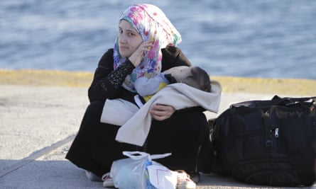 A refugee woman sits on the ground in Piraeus port.