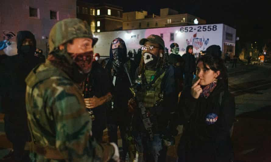 A militia man and armed protester engage in conversation in Kenosha, Wisconsin.