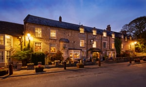 Exterior of the Bull Hotel, Fairford, at night with lights on inside and out.